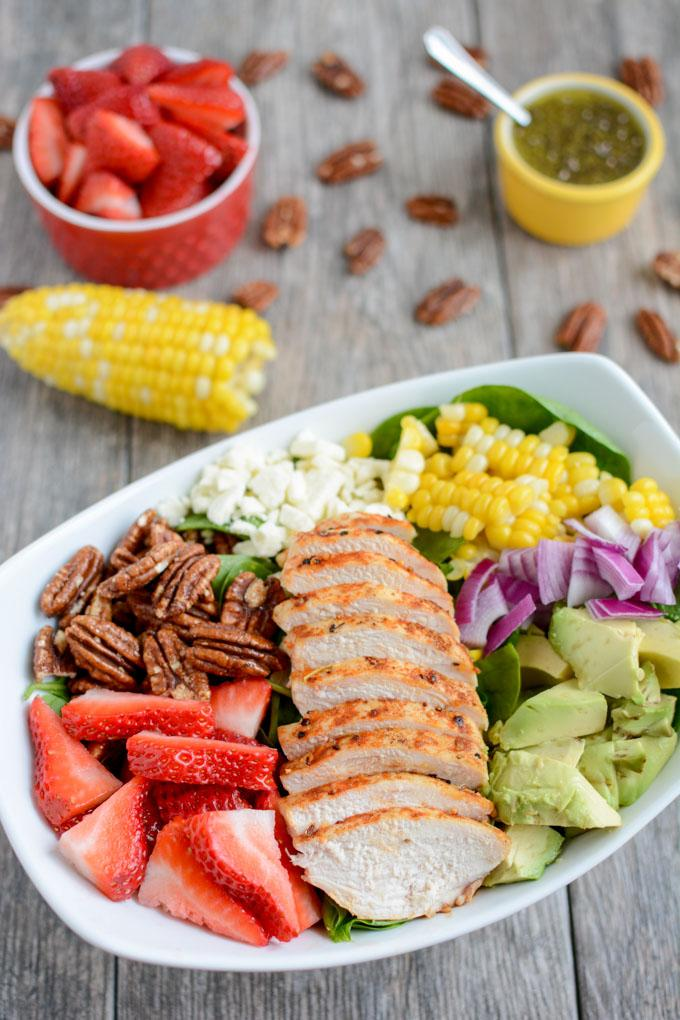 This Strawberry Chicken Spinach Power Salad is perfect for summer! It's packed with protein, fresh produce & nuts and topped with a lemon poppyseed dressing. A great recipe for lunch or dinner!