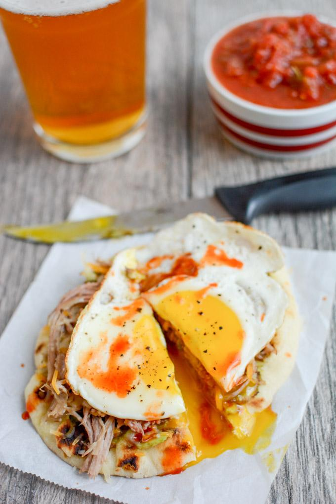 This Pork and Egg Breakfast Pizza is perfect for a late morning football party or tailgating. Cook the pork overnight, then just shred, assemble and top with an egg!