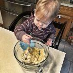 toddler in the kitchen mashing banana