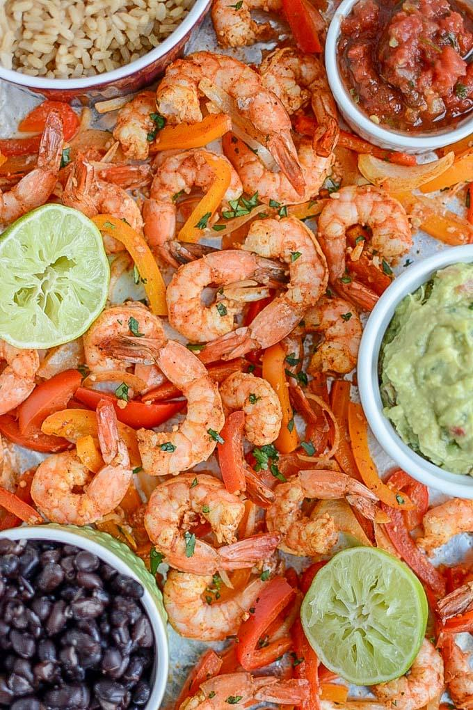 Sheet Pan Shrimp Fajitas with rice, beans, guacamole and salsa