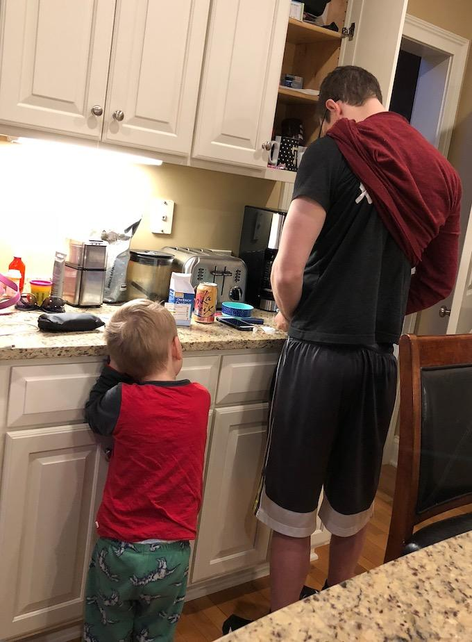 toddler watching dad check blood sugar