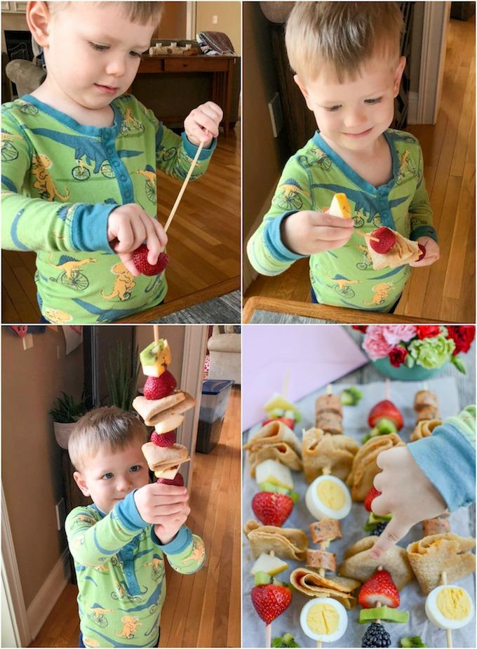 Toddler assembling fruit crepe kabobs