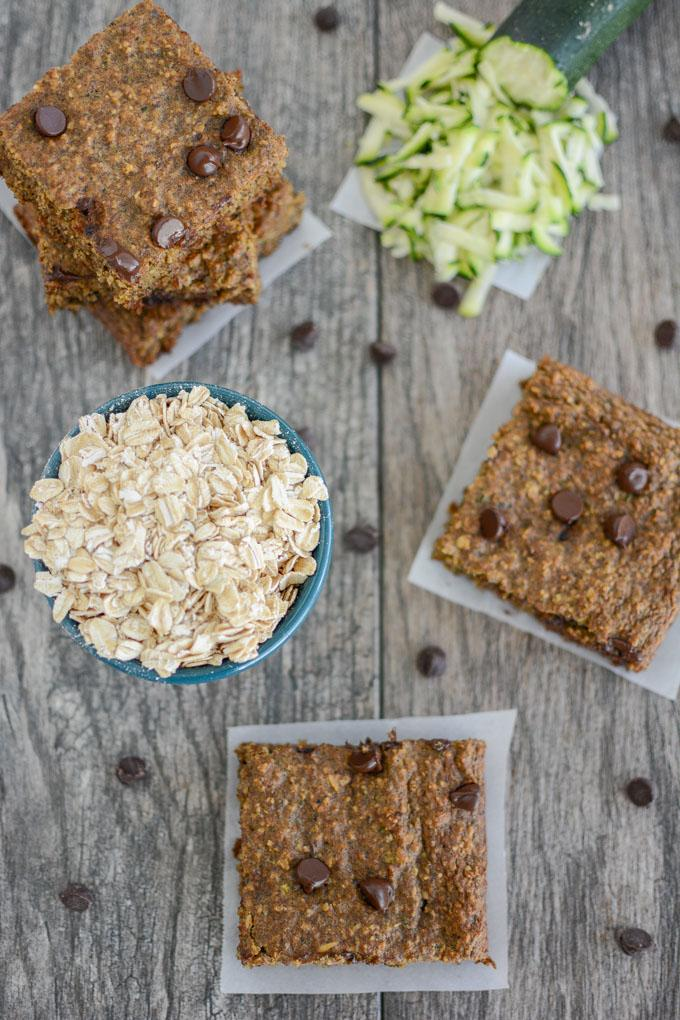 overhead shot of zucchini oat bars with bowl of oats and shredded zucchini
