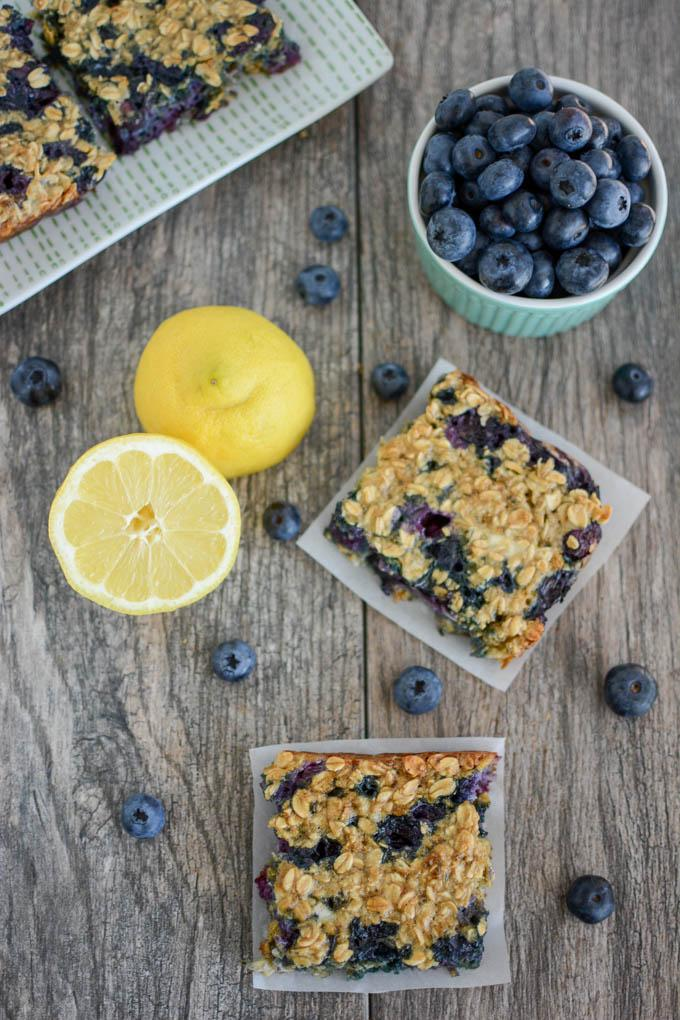 Lemon Blueberry Cheesecake Oat Bars overhead with lemon cut in half and bowl of blueberries
