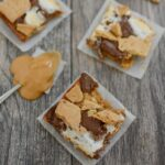 three easy peanut butter s'mores bars with a spoonful of peanut butter