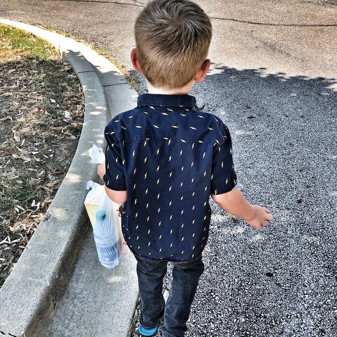 toddler giving bag to person in need