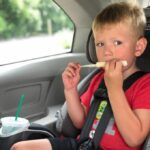 child eating string cheese in the car