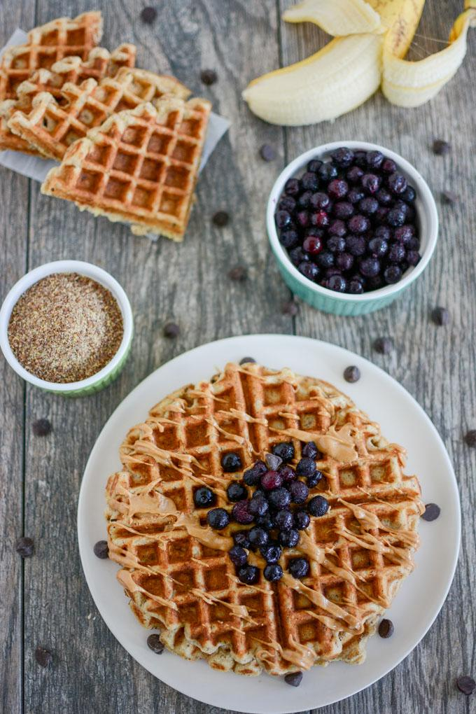 Overhead shot of Banana Flax Waffles topped with blueberries and peanut butter