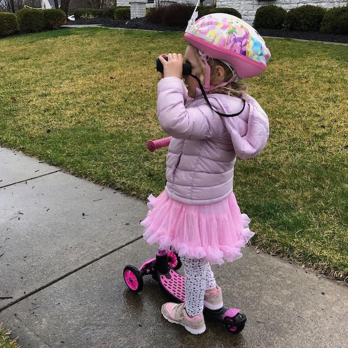 toddler on a scooter with binoculars