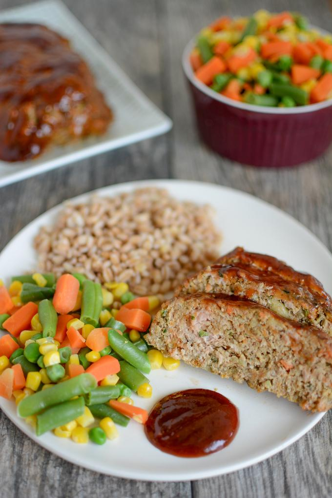 turkey meatloaf with vegetables on plate with steamed mixed vegetables and farro